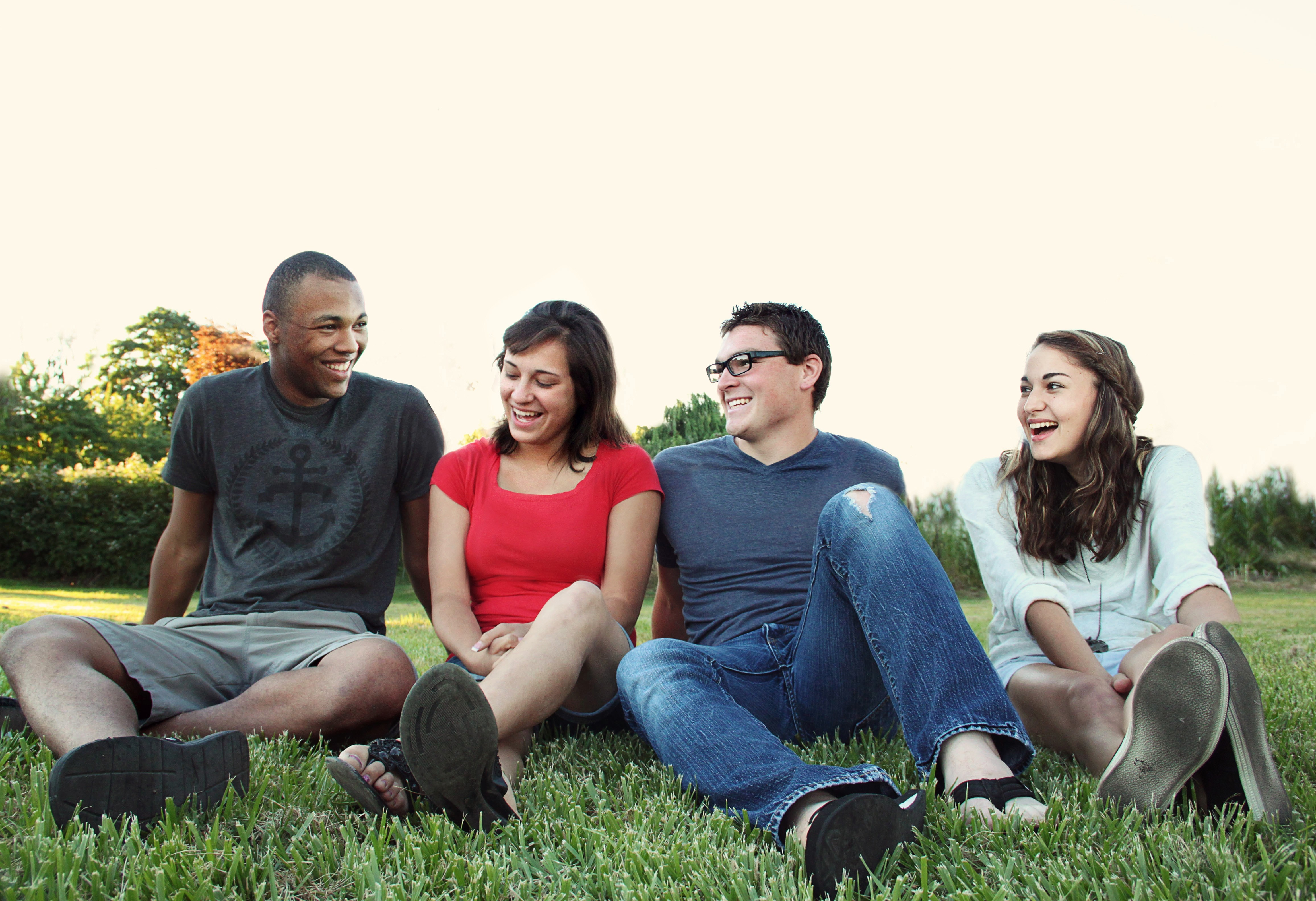 The Image shows four smiling young people in jeans and tshirts seated on grass.