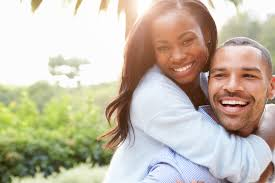 Image appears to be heterosexual African American couple smiling and hugging in outdoor setting
