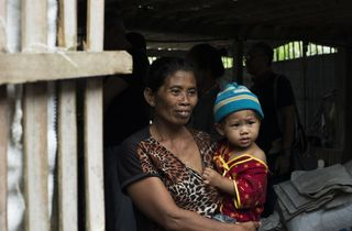 Mark Chaves/Unsplash Women carrying child near door
