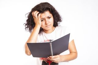 Confused young woman reading a book  Flickr by CollegeDegrees360 on Wikimedia commons