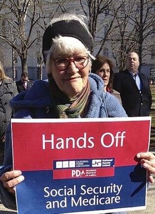 https://upload.wikimedia.org/wikipedia/commons/a/a8/Nurse_holding_red_white_and_blue_sign_-_Hands_Off_Social_Security_and_Medicare.jpg