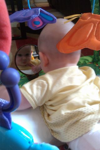 Baby looking at her reflection in mirror