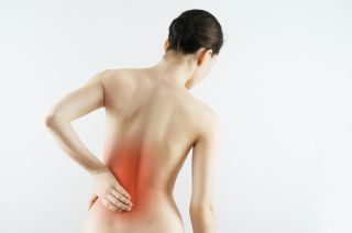 Young woman touching her back in pain