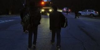 Students approaching schoolbus in morning darkness.