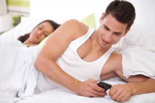 Young man texting his mistress while in bed with his wife