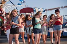 Group of teenage girls all texting their friends