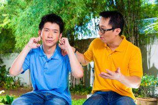 Father tries to talk to teenage son who is plugging his ears with his fingers