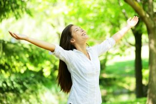 Woman wearing white with arms outstretched in nature