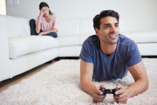 Man plays videos while girlfriend is mad on the couch