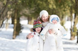 Happy mother and two children play outside in the snow