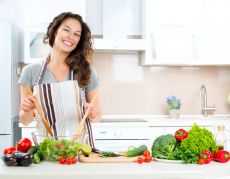 Happy woman in kitchen preparing fresh vegetables.