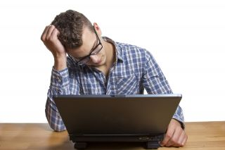 Young man sits hopelessly in front of lap top.