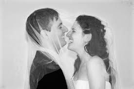 Wedding couple face to face with her veil over his head too.