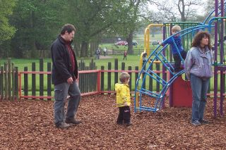 A woman and man together with two small children at a playground outside.