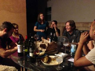 A group of white people seated at a table inside with bread and wine, chatting.