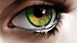 Close-up on a hazel eye with a tear falling down on to white skin.
