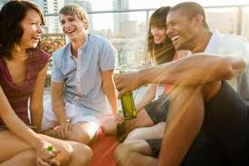 Four smiling young people chatting in an urban room.