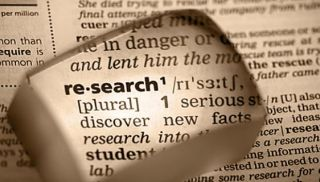 The word research magnified on a page in a dictionary.