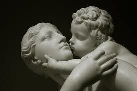 Stone statue of child in woman's arms kissing woman on cheek