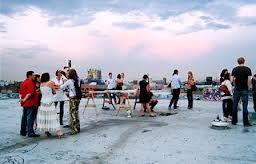 A group of people smiling and chatting on a beach at sunset.