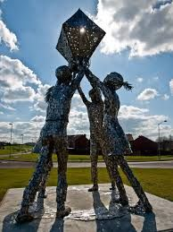 A statue of four silver people holding up an oddly shaped box together