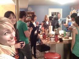 A party of people standing around a kitchen talking and drinking.