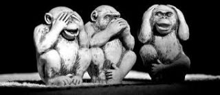 Black and white photo of statues of 3 monkeys, covering eyes, ears, and mouth.