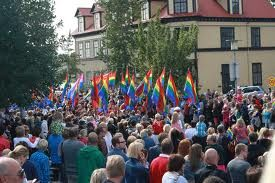A crowd of people outside with rainbow flags