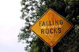 A road sign that reads Falling (in love written in handwriting) Rocks