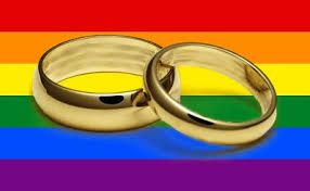 Two gold wedding rings on a rainbow background