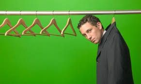 A white man wearing a suit hung from a hanger in a closet, green background