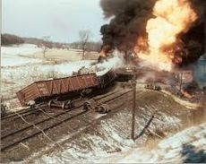 A flaming train wreck on a snowy train track.