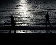 Two people walking away from each other on a beach.