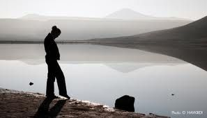 A woman standing alone next to an alpine lake.