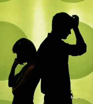 A couple silhouetted back to back against a green background