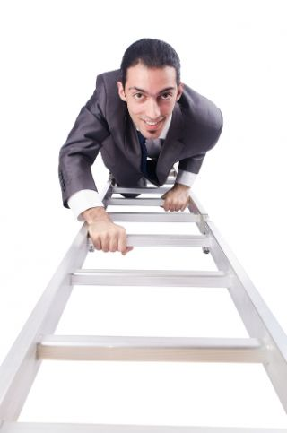 Man in business suit climbing a ladder