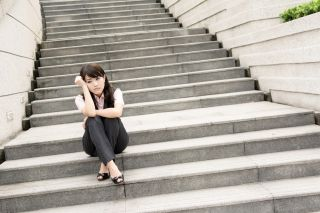 Business woman sitting on the stairs looking dejected
