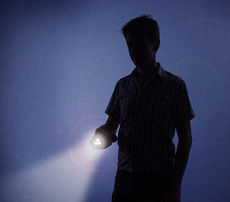 Boy with flashlight at night
