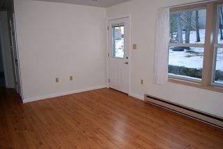 Picture of a completely empty room, with white walls and wooden floors