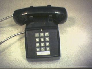Picture of an older commercial push-button phone, in black.