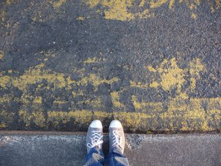 Downward view of two feet in sneakers, getting ready to step into crosswalk