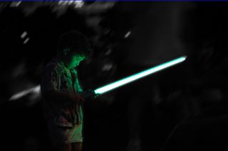 Small boy bathed in green light from toy lightsaber