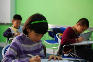 An asian girl in the foreground of a classroom, with two boys in the background.