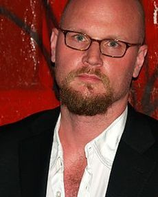 Picture of Augusten Burroughs, white man with glasses, a beard, white shirt.