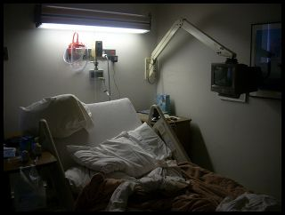 Empty hospital bed with disordered pillow and sheets.