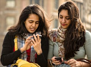Two female friends standing side by side, using their cell phones