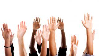 Multi-ethnic hands raised in unison