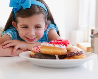 Child eyeing plate of donuts