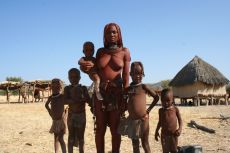 A Himba woman, Mbapaa, and some of her children, nieces and nephews, stand befor
