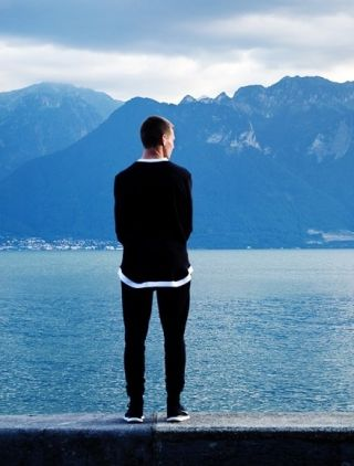 Man stands looking out at the water